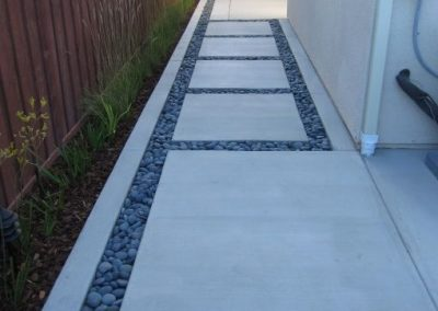 Modern concrete sidewalk with decorative rocks